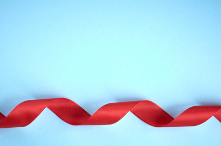 Red ribbon on blue background composition, flat lay and top view photo