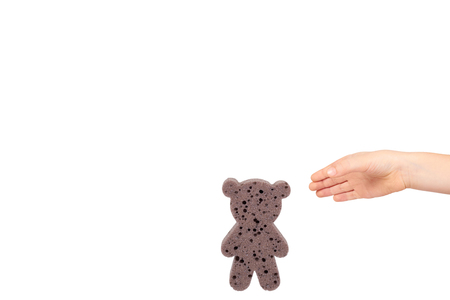 Kids hand with bathroom sponge, soft foam for body care. Isolated on white background. Copy space template