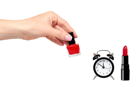 Hand with red nail polish, lipstock and alarm clock. Isolated on white background