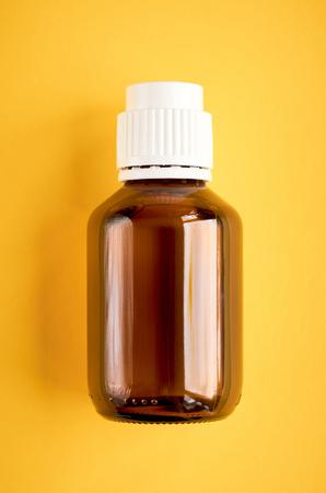 Composición de jarabe en botella de vidrio sobre fondo amarillo, vista plana y superior. Foto de archivo
