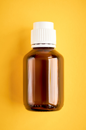 Syrup in glass bottle composition on yellow background, flat lay and top view photo