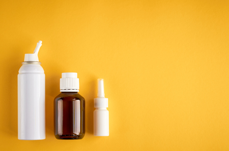 Nasal spray bottle composition, white template bottle on yellow background, flat lay and top view photo