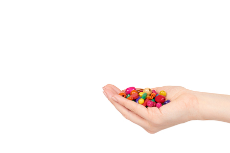 Hand with colored wooden beads, decorative accessory for hand made. Isolated on a white background. Copy space template