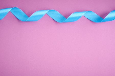 Blue ribbon on purple background composition, flat lay and top view photo