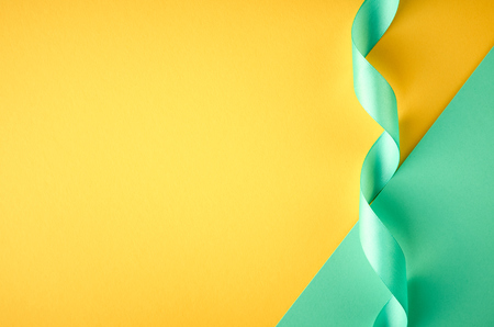 Green ribbon on green and yellow background composition, flat lay and top view photo 스톡 콘텐츠