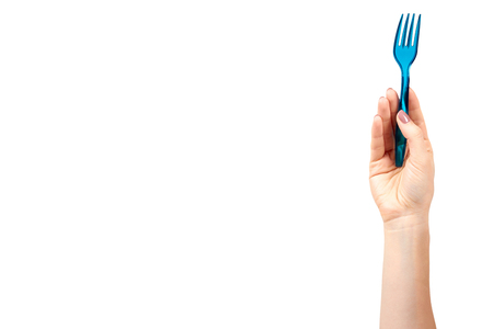 Hand with blue plastic fork, disposable utensil. Isolated on white background. Copy space template