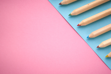 Wooden color pencils on blue background, flat lay composition and top view photo