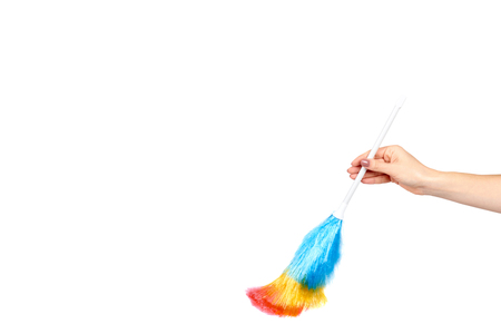 Hand with soft colorful duster, synthetic feather broom, fluffy cleaner. Isolated on white background. Copy space template 스톡 콘텐츠