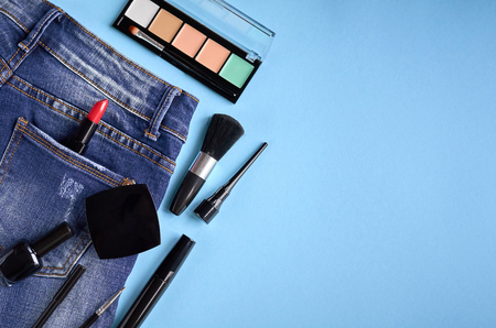 Different makeup products composition with jeans on blue background, flat lay and top view photo
