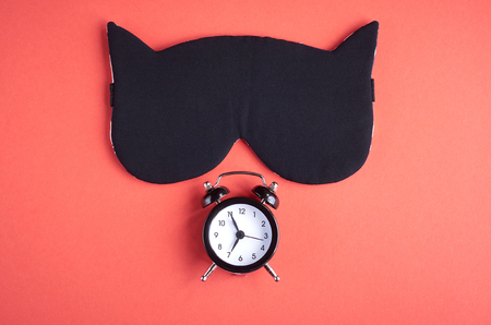 Black sleep mask with clock on pink background composition, cat mask with ears, flat lay and top view photo