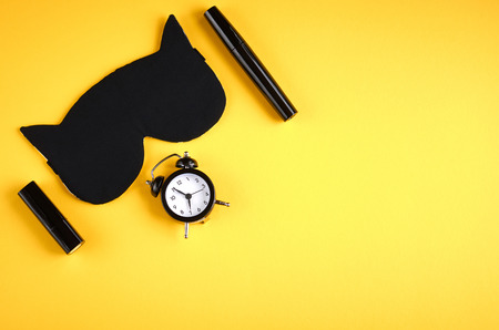 Black sleep mask with clock on yellow background composition, cat mask with ears, flat lay and top view photo