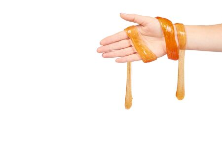 kid playing orange slime with hand, transparent toy. Isolated on white background. Copy space template Фото со стока
