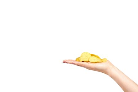 Hand with golden color potato chips, crunchy and wavy. Isolated on white background. Copy space template