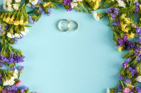 Golden rings with colored flowers on blue background composition, wedding template. Flat lay and top view photo