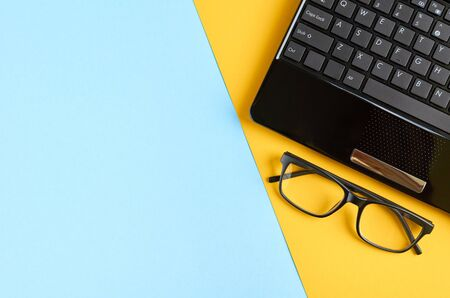 Black glasses and laptop keyboard on blue and yellow background composition. Flat lay and top view photo 写真素材