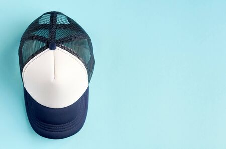 Baseball cap on blue background composition. Flat lay and top view photo