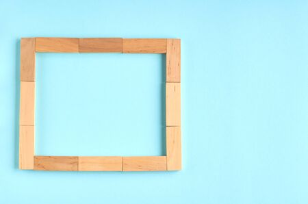 Brown wooden blocks frame shape idea on blue background composition. Flat lay and top view photo 写真素材