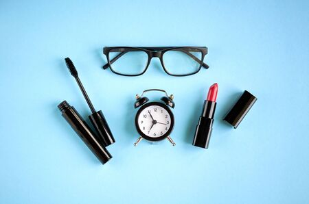 Black glasses, alarm clock, mascara and red pomade on blue background composition. Flat lay and top view photo 写真素材