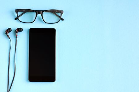 Black glasses, cellphone and headphones on blue background composition. Flat lay and top view photo 写真素材