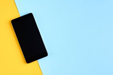 Black cellphone on yellow and blue background composition, mobile phone. Flat lay and top view photo 写真素材