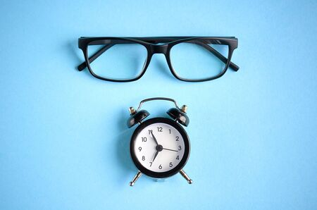 Black glasses and alarm clock on blue background composition. Flat lay and top view photo