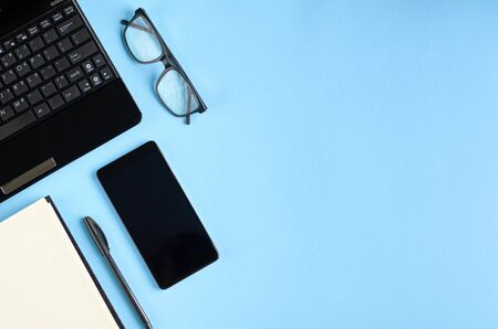 Black glasses, cellphone, paper notebook and laptop keyboard on blue background composition. Flat lay and top view photo