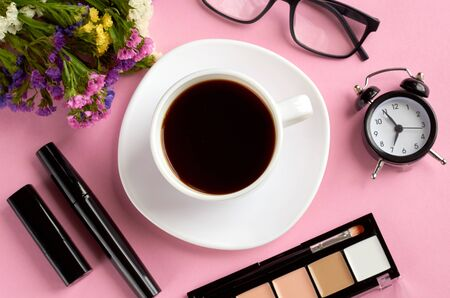 Coffee cup, alarm clock, flowers, mascara and glasses on pink background composition. Flat lay and top view photo