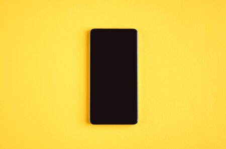 Black cellphone on yellow background composition, mobile phone. Flat lay and top view photo