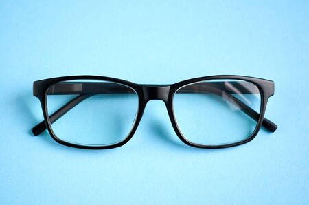 Black glasses on blue background composition, eyeglasses. Flat lay and top view photo 写真素材