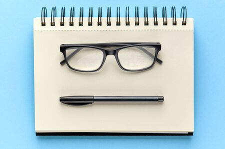 Black glasses, pen and paper notebook on blue background composition. Flat lay and top view photo 写真素材
