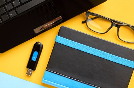 Black glasses, notebook, usb flash and laptop keyboard on blue and yellow background composition. Flat lay and top view photo 写真素材