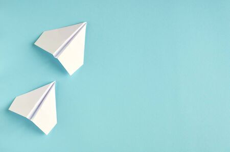 White paper planes on blue background composition. Flat lay and top view photo