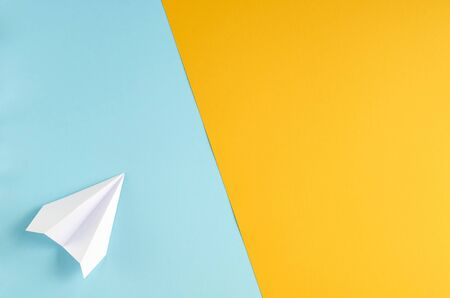 White paper plane on blue and yellow background composition. Flat lay and top view photo 写真素材