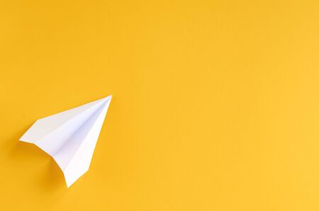 White paper plane on yellow background composition. Flat lay and top view photo