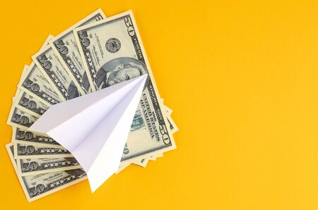White paper plane and money on yellow background composition. Flat lay and top view photo