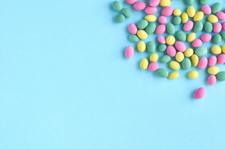 Colored sweets, peanut covered with glaze on blue background composition. Flat lay and top view photo