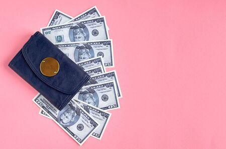 Dark blue leather wallet with money on pink background composition. Flat lay and top view photo