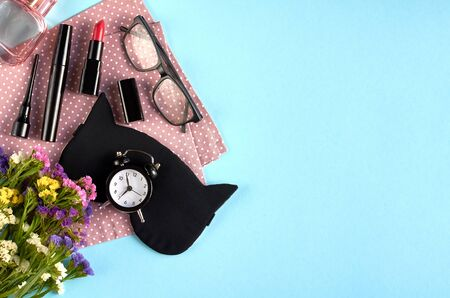 Sleep mask with alarm clock, flowers, mascara and pomade on blue background composition. Flat lay and top view photo