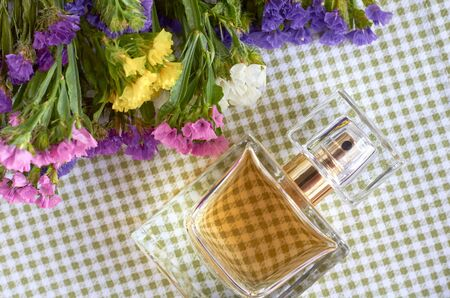 Perfume bottle with flowers on napkin background composition. Flat lay and top view photo
