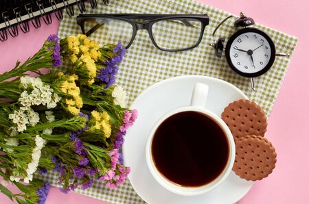 Coffee cup with cookies, alarm clock, flowers, mascara, on pink background composition. Flat lay and top view photo 写真素材