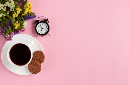 Coffee cup with cookies, alarm clock, flowers, on pink background composition. Flat lay and top view photo 写真素材