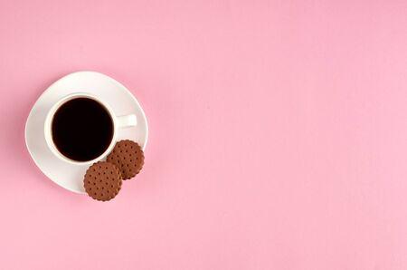 Coffee cup with cookies on pink background composition. Flat lay and top view photo