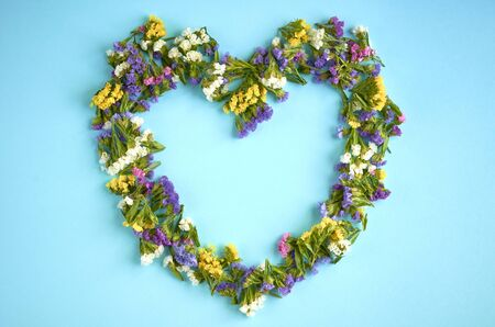 Colored flowers on blue background composition, heart shape. Flat lay and top view photo 写真素材