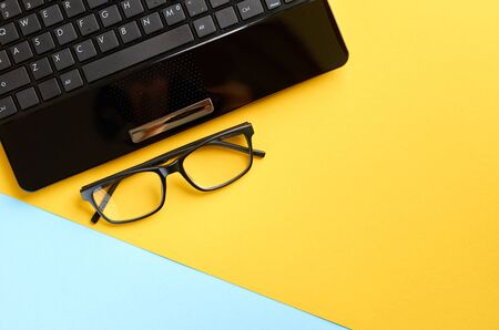 Black glasses and laptop keyboard on blue and yellow background composition. Flat lay and top view photo Stok Fotoğraf