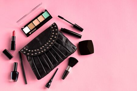 Black leather bag with nail polish, pomade, mascara and eye shadows on pink background composition. Flat lay and top view photo Stok Fotoğraf