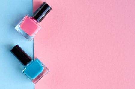 Color nail polish bottles on pink background composition. Flat lay and top view photo Stok Fotoğraf