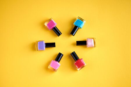 Color nail polish bottles on yellow background composition. Flat lay and top view photo Stok Fotoğraf