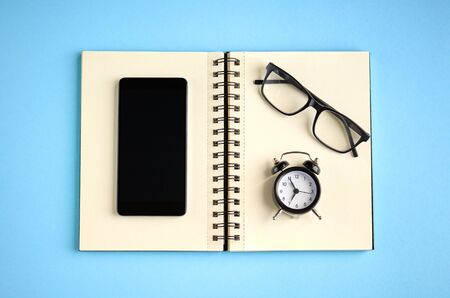 Black glasses, alarm clock, paper notepad and cellphone on blue background composition. Flat lay and top view photo