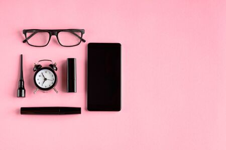 Black glasses, alarm clock, cellphone, mascara and pomade on pink background composition. Flat lay and top view photo