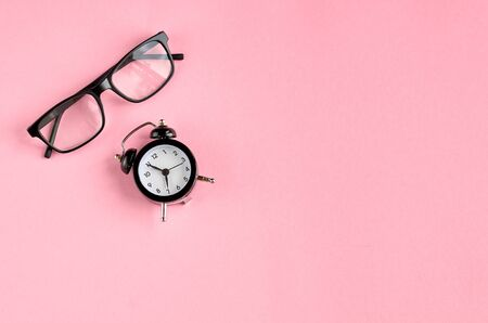 Black glasses and alarm clock on pink background composition. Flat lay and top view photo